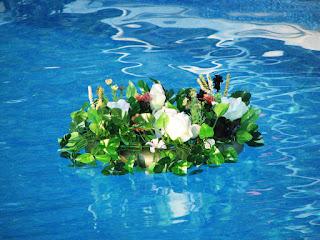 Decoración elegante de flores y velas sobre piscina para bodas