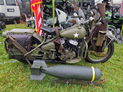 Military motorcycle parked next to an aerial bomb.