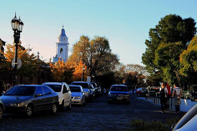 Autos estacionados en calle y al fondo el campanario