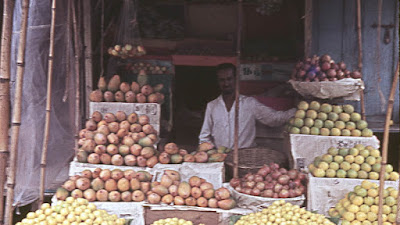 Man sitting among various types of fruit that he is selling