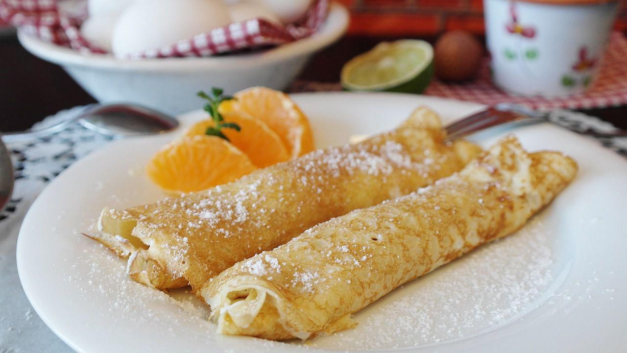 τηγανίτες στο πιάτο με μέλι, κανέλα, ζάχαρη άχνη, πορτοκάλι