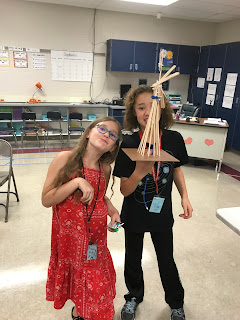 Young girl in red dress and young girl in black shirt and black pants posing with their windmill they made
