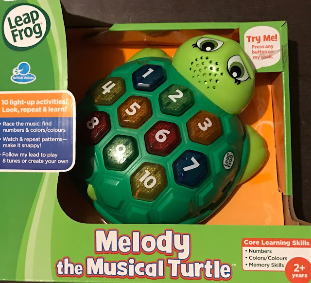 Melody The Musical Turtle in it's packaging (an open box which allows you to press the buttons)