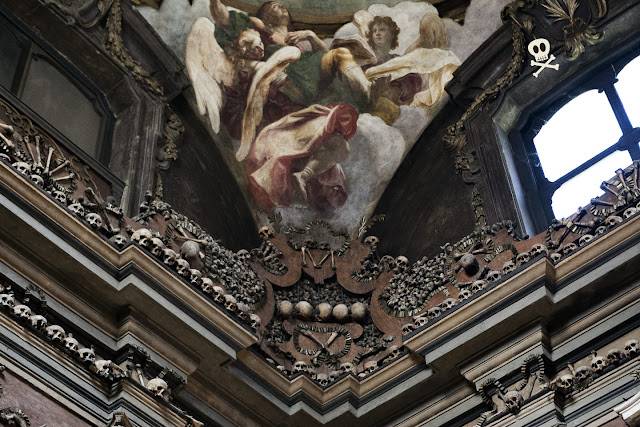 Detalle de una de las pechinas y una de las esquinas de la capilla, con decoración tipográfica, calaveras y huesos pequeños formando figuras.