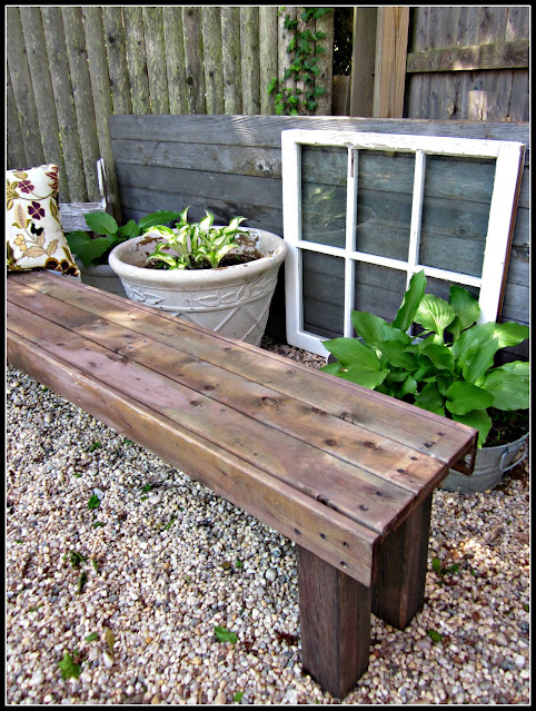stained garden bench in pea gravel garden