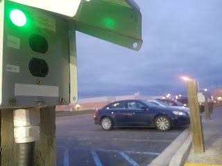 An outlet with a green light lit, in a parking lot