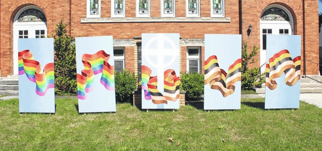 Mural shows a rainbow ribbon coming from the left and a racial harmony flag coming from the right, to join around a cross in the center panel. Located at Peace Community Church in Oberlin; mural by Robert Cothran (photo by VUrbanik).