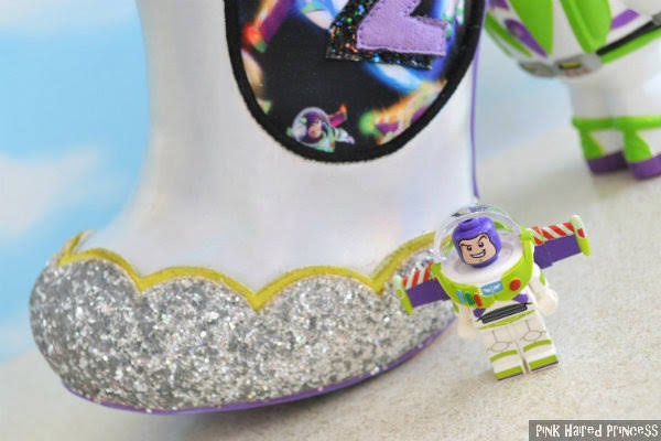 small buzz lightyear figure sitting in front of close up of silver glitter toe of ankle boot