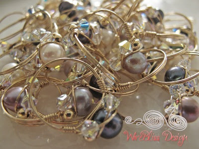 a bunch of wire wrapped sparkly rings with pearls and Swarovski Crystals