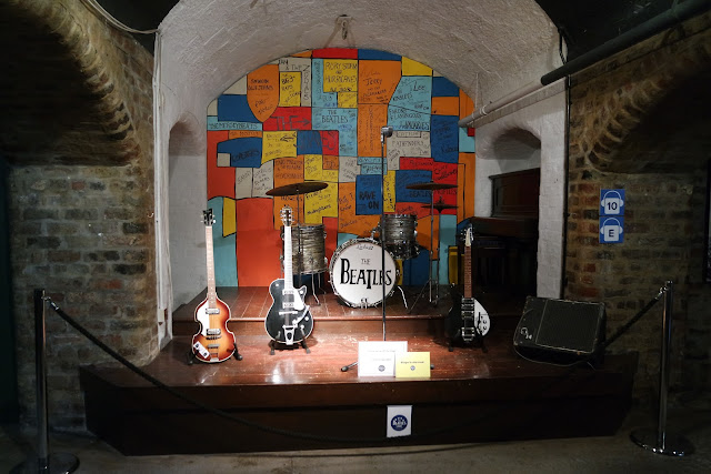 recreation of The Cavern stage with instruments on it and a white wall behind it painted in blocks of different colours and signed by bands who have played on the stage