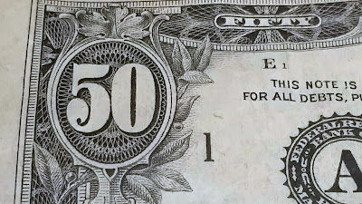 The ornate top left corner of a fifty dollar bill.