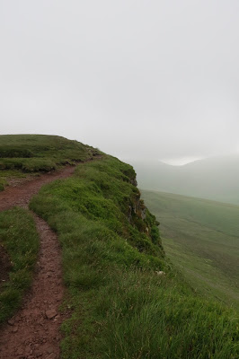 A path along the edge appears clear while more distant views across the valley become hidden in mist.