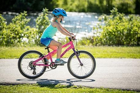A little girl is riding her pink bike