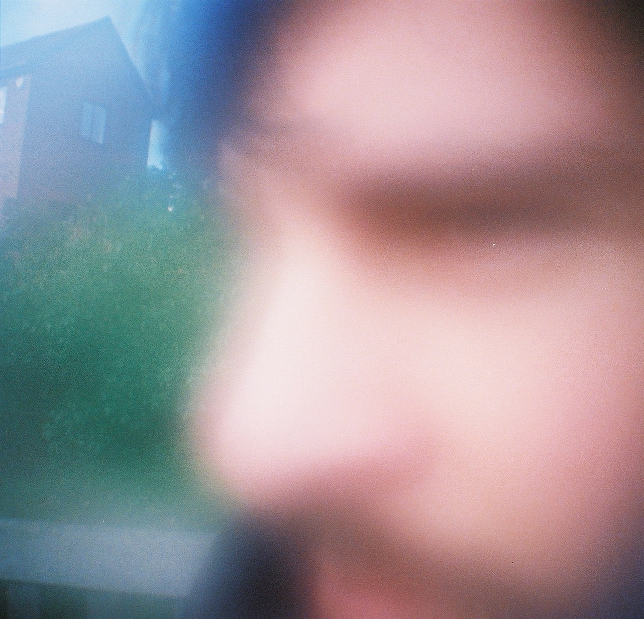 A foggy image of a man's face. Grass can be seen behind him.