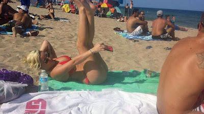Lustige Frau macht Urlaubs-Selfie am Strand