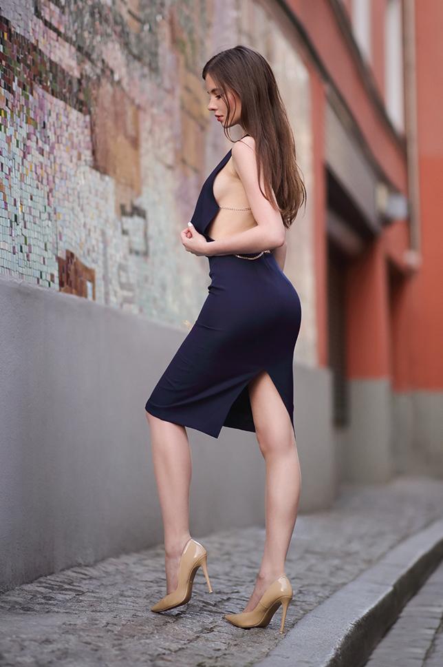 Granatowa sukienka z odkrytym tyłem, beżowe szpilki i cieliste pończochy