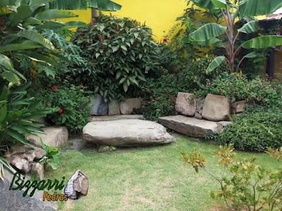 Banco de pedra no jardim, com pedra moledo, e a mesa de pedra com a execução do paisagismo natural.