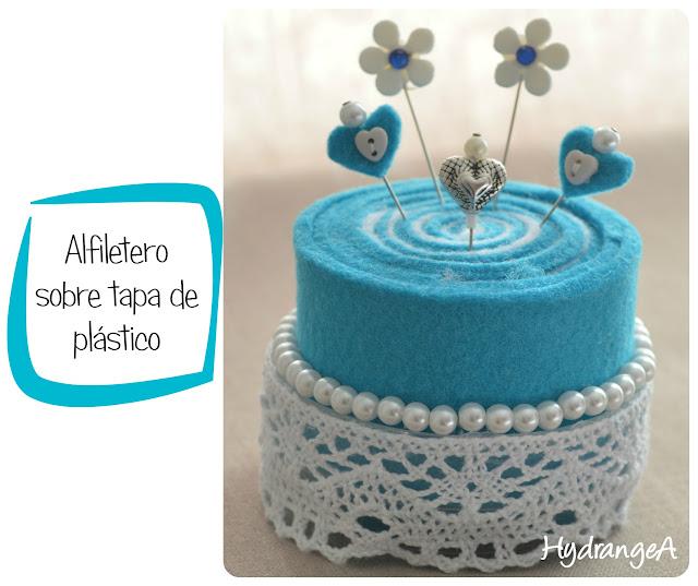 Alfiletero realizado en fieltro azul turquesa y blanco con forma de pastel, decorado con perlas, puntilla y alfileres con formas de flores y corazones.