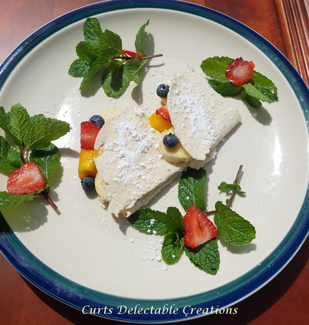 This is a picture of a freshly made Crepe filled with fruit and topped with powdered sugar.