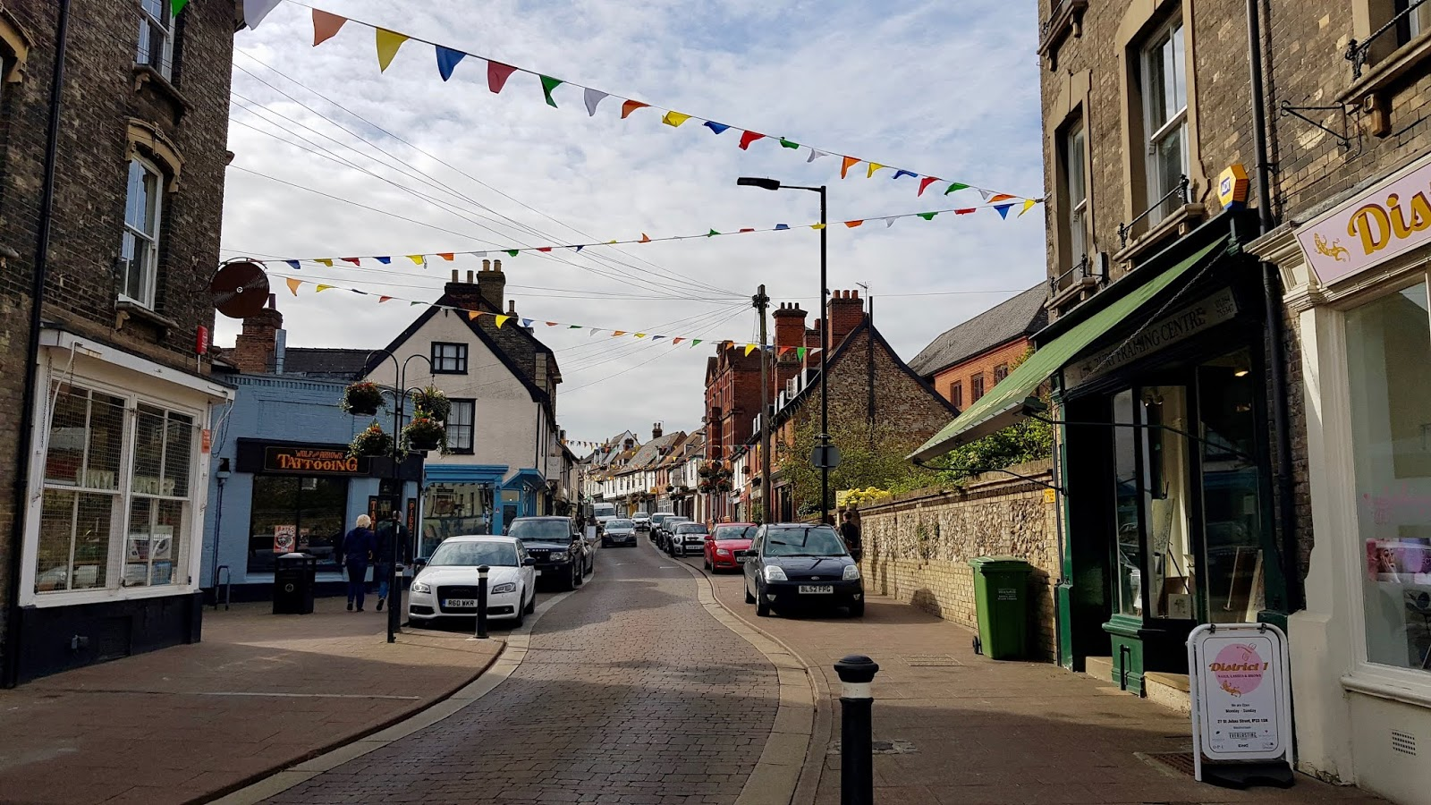 St John's Street, Bury St Edmunds, with colourful independent shops and bunting strung between the houses