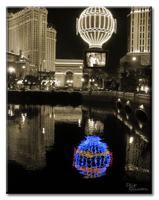 Black and white photo fo Las Vegas with colored hot air balloon reflection in the water
