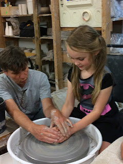 Teaching children centering clay on the potter's wheel by Lori Buff
