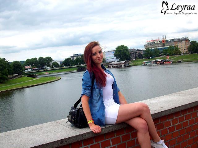 Koszula jeansowa, białe body, biała mini spódnica, białe trampki, kolorowe bransoletki, mała czarna damska torebka na ramię