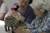 Two ladies looking at a basketry woven ox