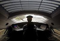 Bir hızlı tren kokpitinde treni süren makinistin arkadan görüntüsü