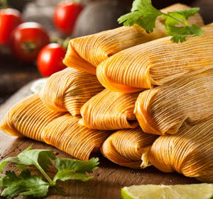 stack of tamales with a sprig of cilantro on top, cherry tomatoes in the background and a lime wedge on the side