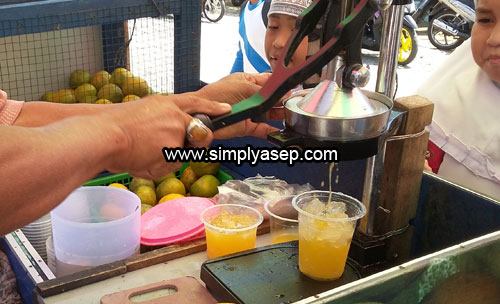 MURAH : Seorang penjual es Jeruk peras sedang melayani pelanggan setianya di sekolah. Foto Asep Haryono