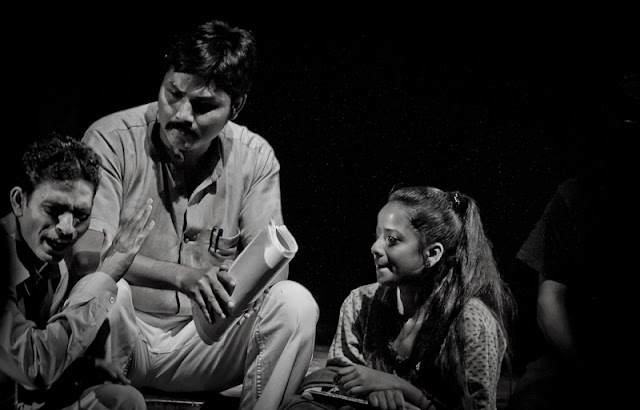 Professor Hanif, played by Palash Protim Mech, with his students. He is shown to be a thoughtful and liberal man who is a successful writer as well as a teacher popular with his students. Throughout the play, this character is constantly struggling against being treated differently because he belongs to a minority religious community.