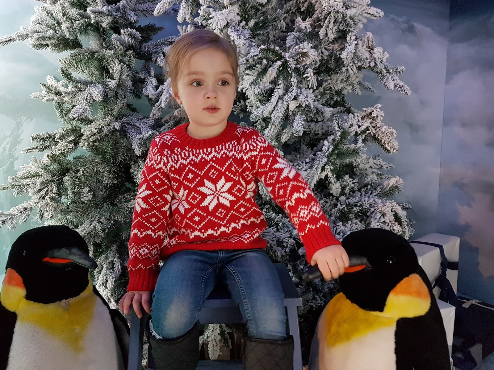girl wearing red christmas jumper posing with penguins at harrods christmas grotto 2016