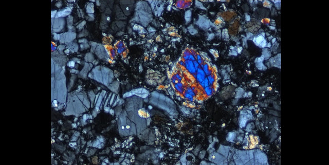 Cross-polarized light image (0.07mm field of view) of a portion of the interior of the lunar 'Rusty Rock' impact melt breccia. Grey minerals are plagioclase grains and bright colored grains are pyroxene grains. (Photo: NASA/JSC)