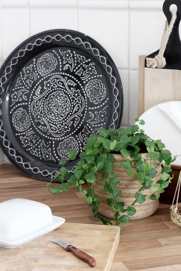 Holzübertopf von Tierlantijn darin eine Grünpflanze, weißes HK Living Brettchen und schwarz weißes Tablett