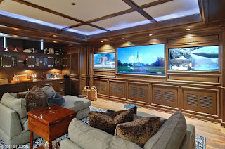 An image of beautiful living room with three TV's and white couches