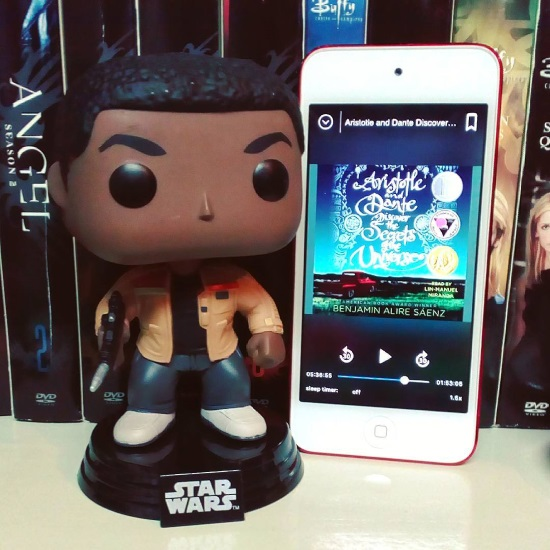 A large-headed Funko Pop bobblehead of Finn from Star Wars stands next to a red-bordered iPod with Aristotle and Dante Discover the Secrets of the Universe's cover on it. The cover features the title in swirling white letters above a dark blue sky with a red pickup truck beneath it.