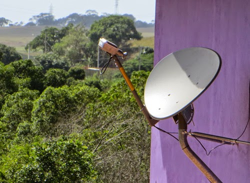 Foto de uma antena de internet via satelite. Ela se aparenta com uma antena de tv via satelte, com um disco de um metro de diâmetro, e embaixo dela, para frente, uma haste com um dispositivo voltado para o centro deste disco capta as ondas do satélite.