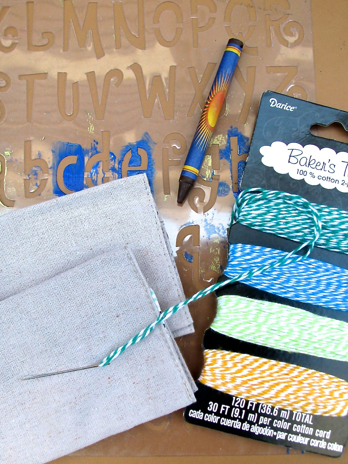 Stencil, crayon, fabric card holders, baker's twine and needle