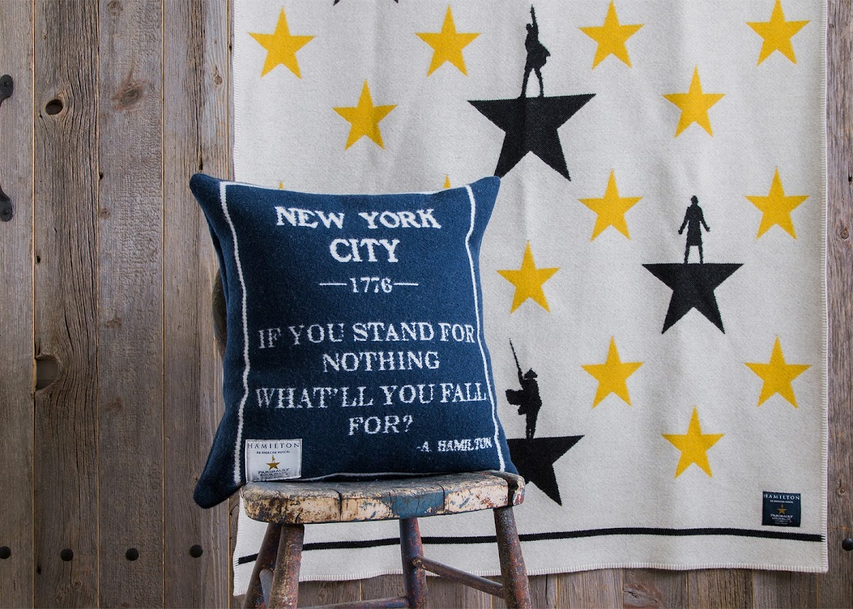 photo of the Hamilton blanket hanging up, decorative pillow on a chair