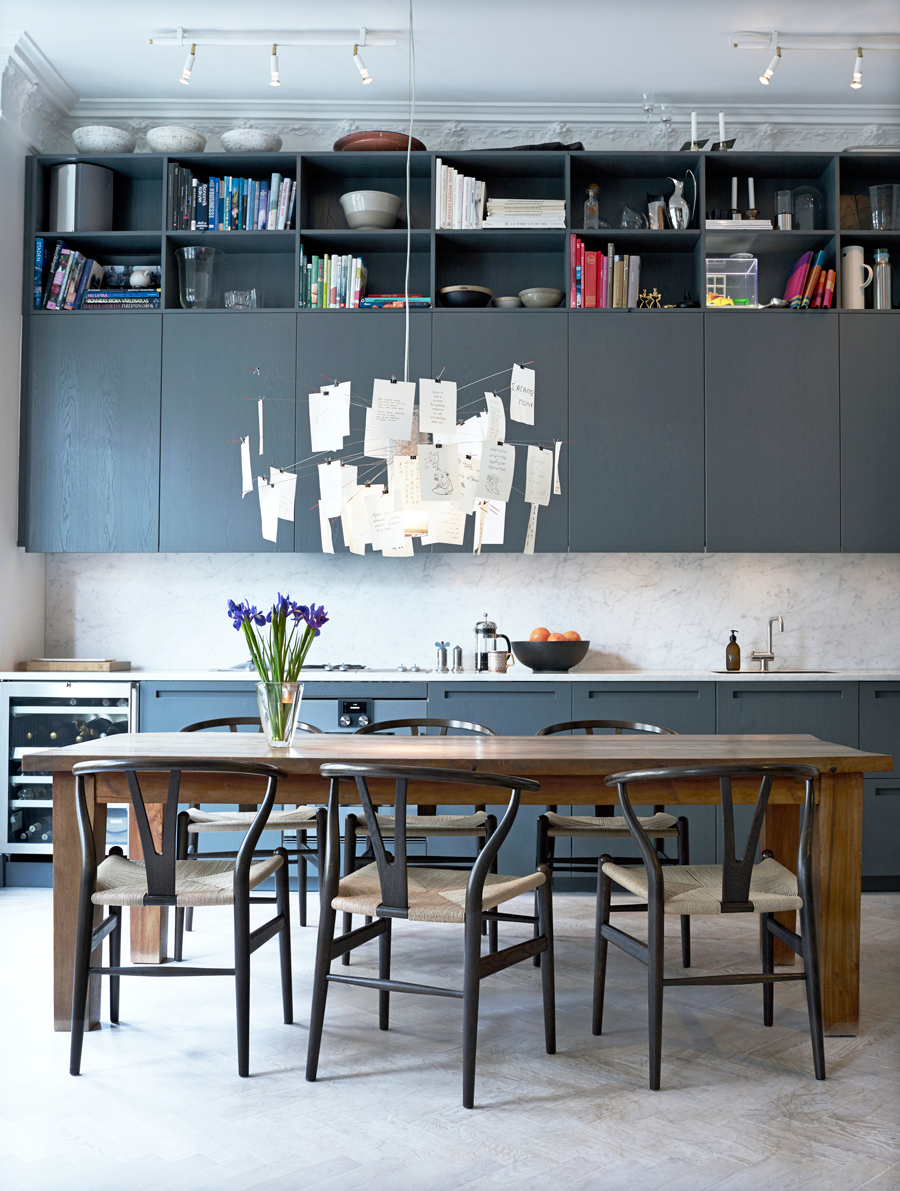 gray kitchen with marble backsplash and wishbone chair by hans wegner