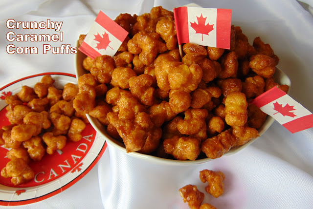 Crunchy Caramel Corn Puffs in serving bow with little Canadian flags are stuck in the puffs .  Individual servings are on Canada Day paper plates.