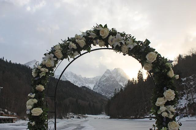 Rosenbogen am See mit Bergpanorama, Eisblau und Leuchtrot, Winterhochzeit in den Bergen von Bayern, Riessersee Hochzeitshotel Garmisch-Partenkirchen, Winter wedding in Bavaria, Germany