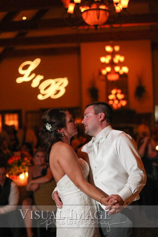 Bride and groom sharing first dance at The Legend of Brandybrook with wall monogram in background