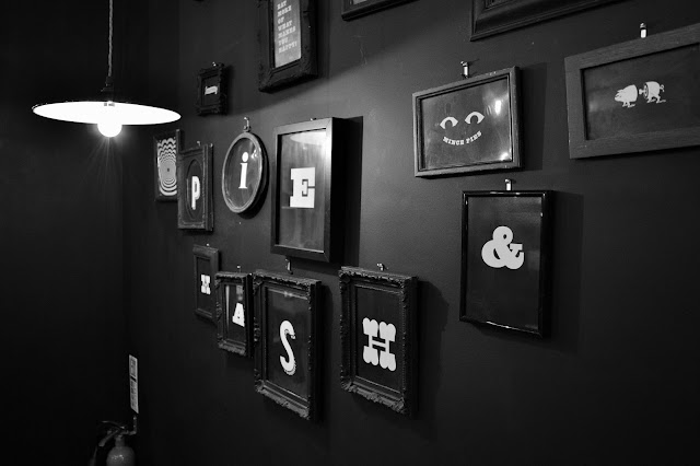 a black and white wall display with pie & mash written across several picture frames.