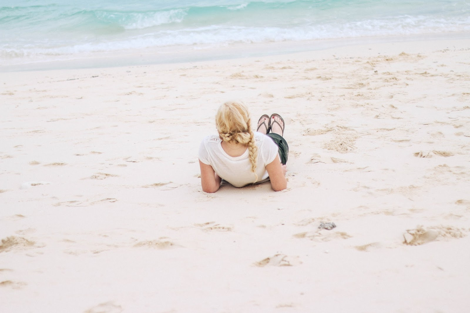 Fashion and Travel Blogger GlobalFashionGal (Brianna Degaston) wearing a white boho top and army green shorts at Bamboo Island in the Phi Phi Islands, Thailand.