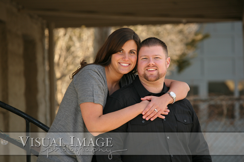 Woman hugging her fiance for engagement portrait in downtown Cedarburg