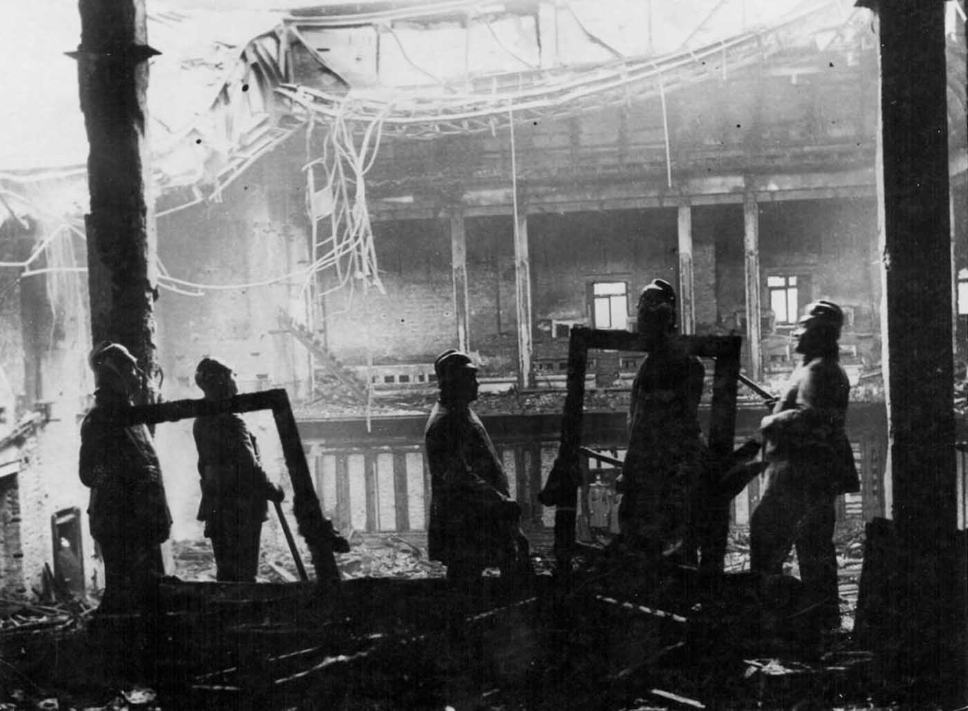 Firemen surveying the ruins following the Reichstag fire.