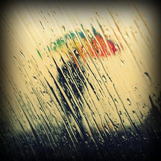 sombra de hombre con paraguas de colores, gotas de lluvia en una ventana