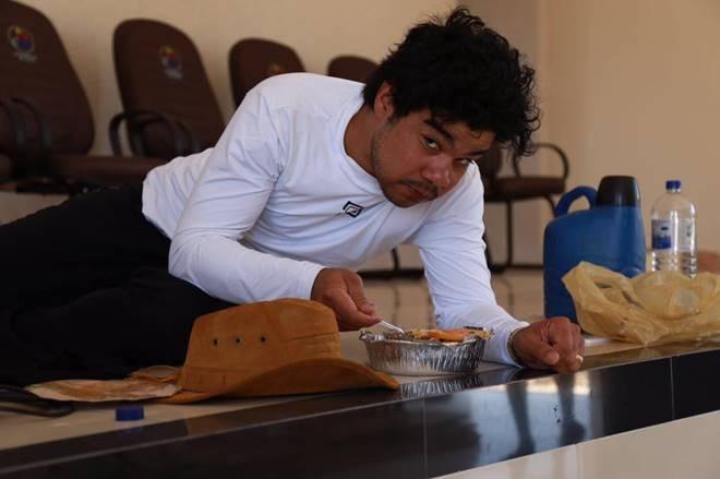 Samuel Mariano comendo marmita no chão da igreja